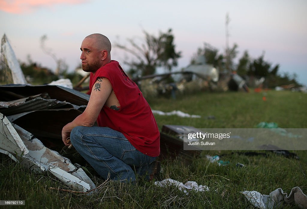 Mark Reynolds pauses while looking through debris to find personal items after a series of tornadoes that ripped through the area a day earlier on June 1, 2013 in El Reno, Oklahoma. A series of tornadoes ripped through the area on Friday evening killing at least nine people, injuring many others and destroying homes and buildings.
