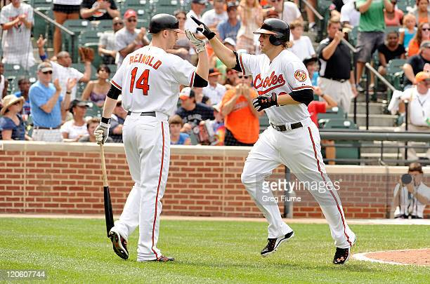 Mark Reynolds the Baltimore Orioles celebrates with Nolan Reimold after hitting a home run in the seventh inning against the Toronto Blue Jays at...