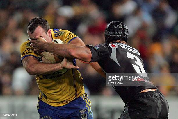 Mark Riddell of the Eels receives a hand to the face from Tony Martin of the Warriors during the round 11 NRL match between the Parramatta Eels and...