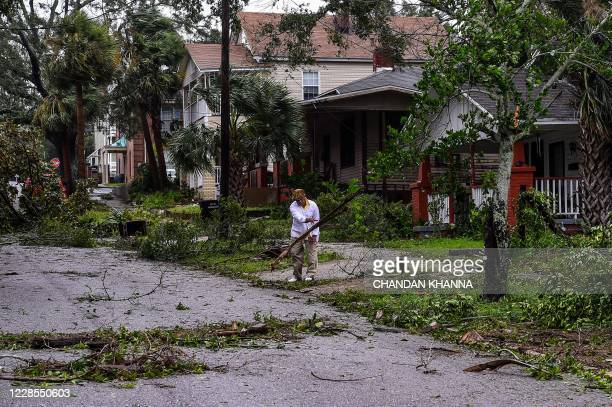 TOPSHOT Mark Robinson removes the branch of a tree after Hurricane Sally outside this home in Pensacola Florida on September 16 2020 Hurricane Sally...
