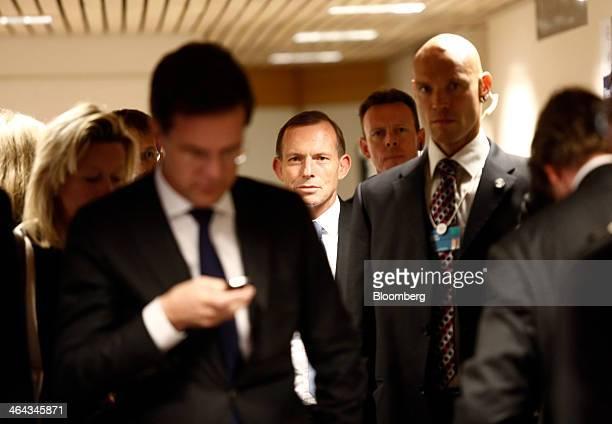 Mark Rutte Dutch prime minister left looks as his mobile handset as Tony Abbott Australia's prime minister center walks between venues during a break...