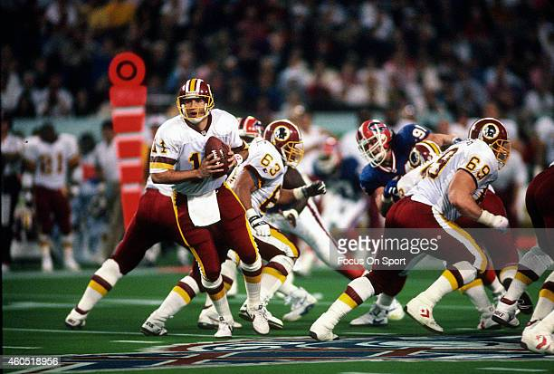 Mark Rypien of the Washington Redskins turns to hand the ball off against the Buffalo Bills during Super Bowl XXVI at the Metrodome in Minneapolis...