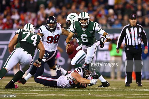Mark Sanchez of the New York Jets is sacked by JJ Watt of the Houston Texans in the fourth quarter at MetLife Stadium on October 8 2012 in East...