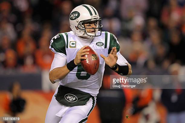 Mark Sanchez of the New York Jets rolls out of the pocket to pass in the first quarter against the Denver Broncos at Invesco Field at Mile High on...