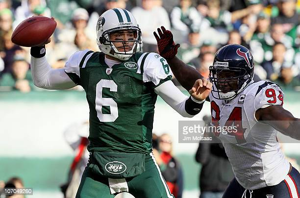 Mark Sanchez of the New York Jets throws a pass under pressure from Antonio Smith of the Houston Texans on November 21 2010 at the New Meadowlands...
