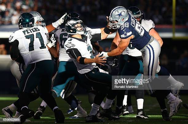 Mark Sanchez of the Philadelphia Eagles is hit by Tyrone Crawford of the Dallas Cowboys in the first half at ATT Stadium on November 27 2014 in...