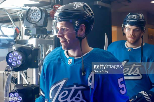 Mark Scheifele and Adam Lowry of the Winnipeg Jets head to the ice prior to puck drop against the Chicago Blackhawks at the Bell MTS Place on...
