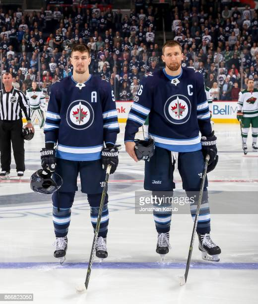 Mark Scheifele and Blake Wheeler of the Winnipeg Jets stand on the ice during the singing of the National anthems prior to puck drop against the...