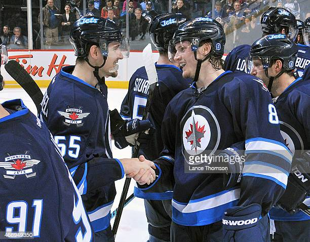 Mark Scheifele and Jacob Trouba of the Winnipeg Jets shake hands as they celebrate a 21 shootout victory over the St Louis Blues on March 19 2015 at...
