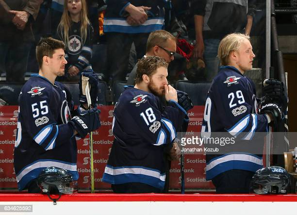 Mark Scheifele Bryan Little and Patrik Laine of the Winnipeg Jets stand on the bench during the singing of the National anthems prior to puck drop...
