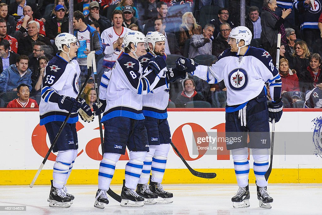 Mark Scheifele #55, Jacob Trouba #8, Zach Bogosian #44, and Blake Wheeler #26 of the Winnipeg Jets celebrate the third period goal of Jacob Trouba against the Calgary Flames during an NHL game at Scotiabank Saddledome on January 16, 2014 in Calgary, Alberta, Canada. The Jets defeated the Flames 5-2.