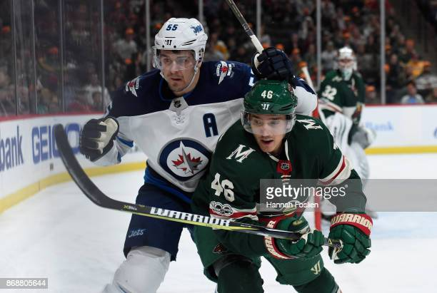 Mark Scheifele of the Winnipeg Jets and Jared Spurgeon of the Minnesota Wild skate after the puck during the first period of the game on October 31...