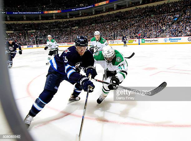Mark Scheifele of the Winnipeg Jets and Johnny Oduya of the Dallas Stars battle for the puck along the boards during third period action at the MTS...