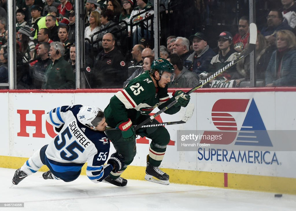 Mark Scheifele #55 of the Winnipeg Jets and Jonas Brodin #25 of the Minnesota Wild skate after the puck during the first period in Game Three of the Western Conference First Round during the 2018 NHL Stanley Cup Playoffs at Xcel Energy Center on April 15, 2018 in St Paul, Minnesota. The Wild defeated the Jets 6-2.