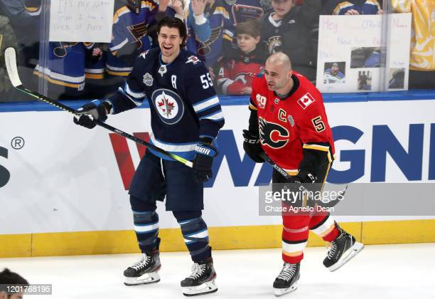 Mark Scheifele of the Winnipeg Jets and Mark Giordano of the Calgary Flames share a laugh on the ice during the 2020 NHL AllStar Skills competition...