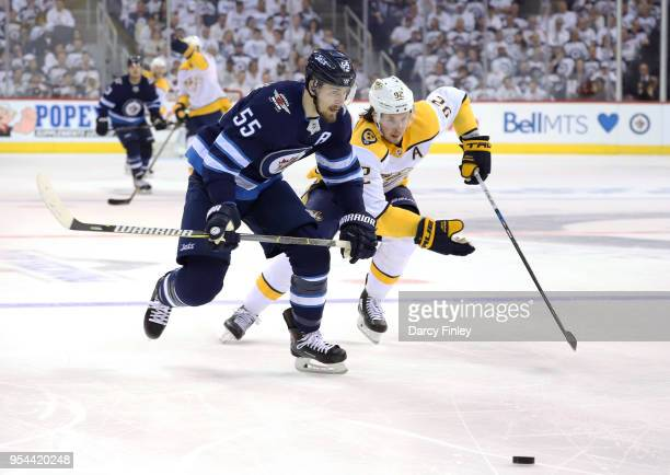 Mark Scheifele of the Winnipeg Jets and Ryan Johansen of the Nashville Predators chase the loose puck down the ice during second period action in...