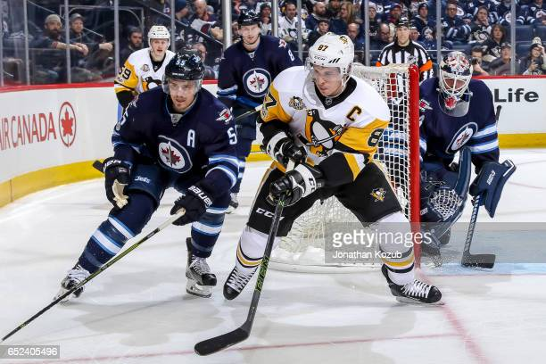 Mark Scheifele of the Winnipeg Jets and Sidney Crosby of the Pittsburgh Penguins keep an eye on the play along the corner boards during third period...