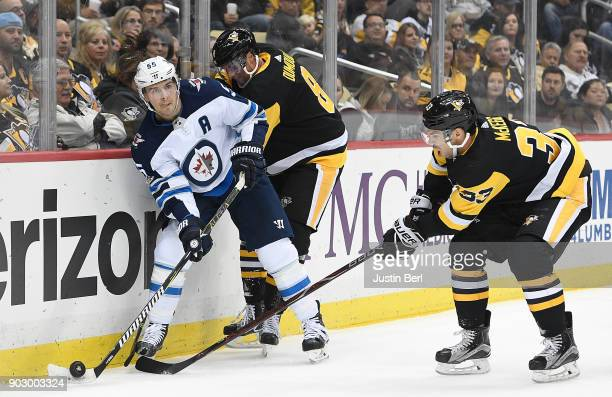 Mark Scheifele of the Winnipeg Jets attempts a pass while being defended by Brian Dumoulin of the Pittsburgh Penguins and Greg McKegg during the game...