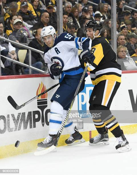 Mark Scheifele of the Winnipeg Jets battles with Brian Dumoulin of the Pittsburgh Penguins for a loose puck along the boards during the game at PPG...