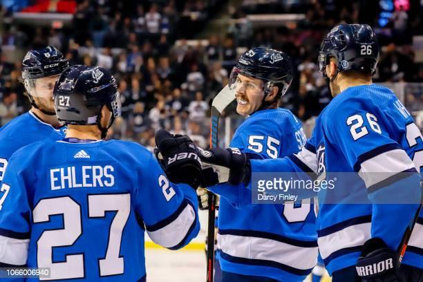 Mark Scheifele of the Winnipeg Jets celebrates his second period goal against the Pittsburgh Penguins with teammates Jacob Trouba Nikolaj Ehlers and...