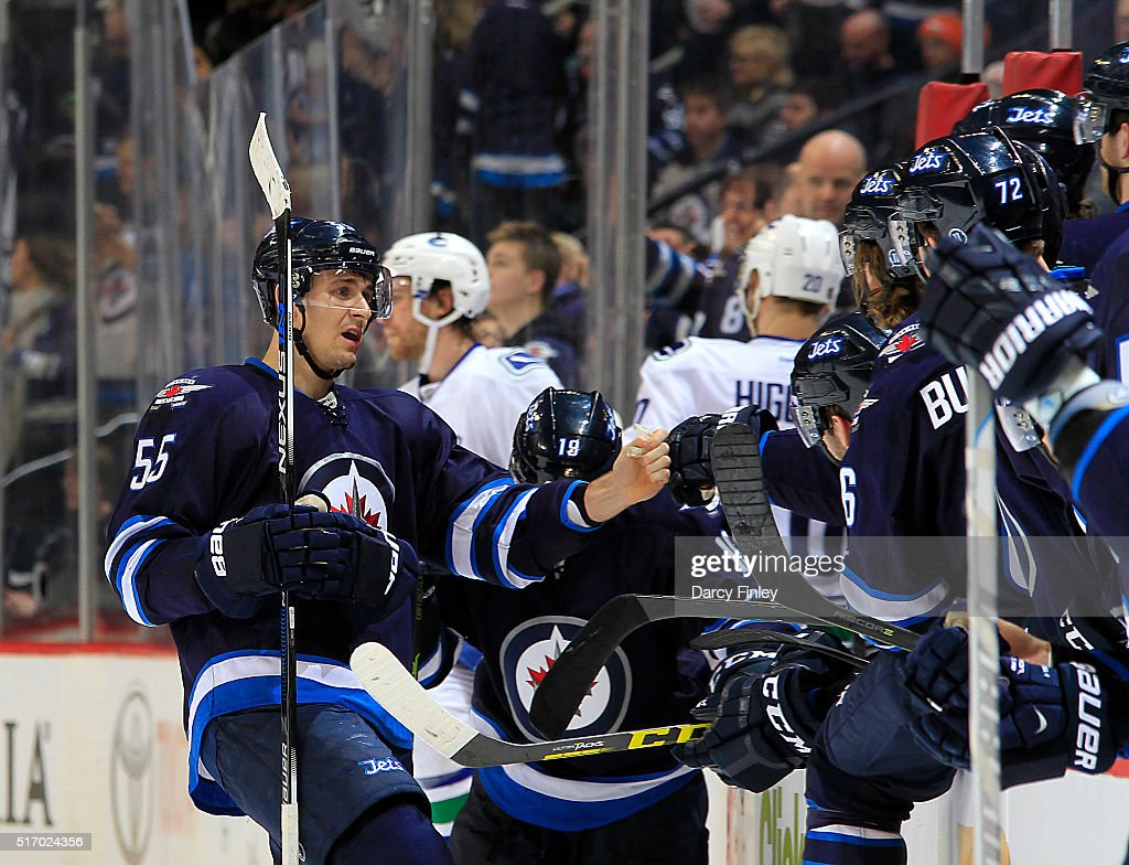 Mark Scheifele #55 of the Winnipeg Jets celebrates his third period empty net goal against the Vancouver Canucks with teammates at the bench at the MTS Centre on March 22, 2016 in Winnipeg, Manitoba, Canada.