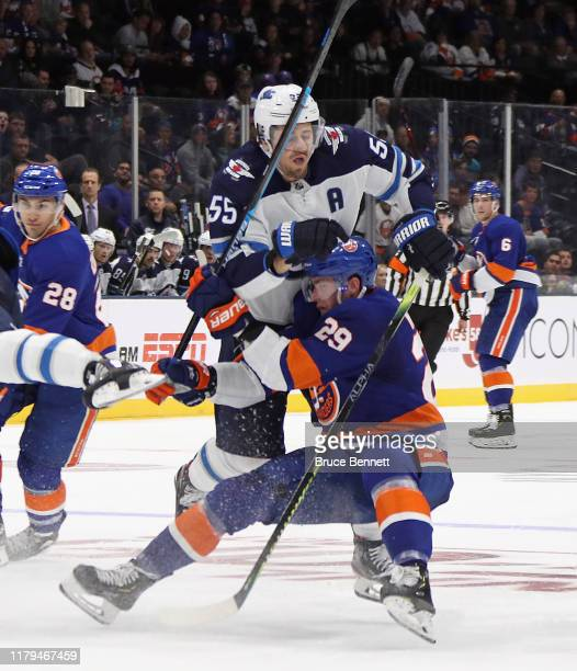 Mark Scheifele of the Winnipeg Jets checks Brock Nelson of the New York Islanders during the second period at NYCB Live's Nassau Coliseum on October...