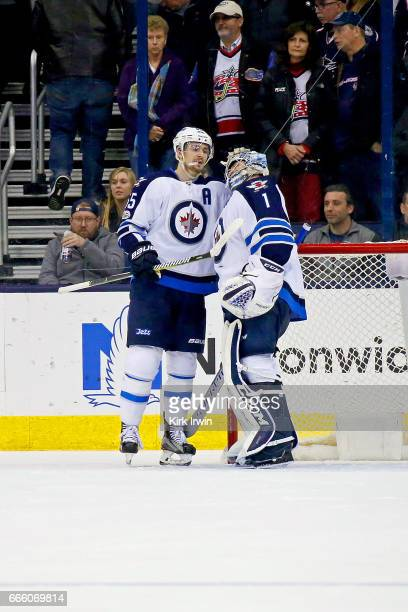 Mark Scheifele of the Winnipeg Jets congratulates Eric Comrie of the Winnipeg Jets after defeating the Columbus Blue Jackets 54 in his NHL debut on...
