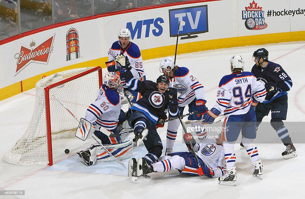 Mark Scheifele #55 of the Winnipeg Jets falls to the ice as he celebrates after scoring the go-ahead goal against Ilya Bryzgalov #80 of the Edmonton Oilers during third period action at the MTS Centre on January 18, 2014 in Winnipeg, Manitoba, Canada.