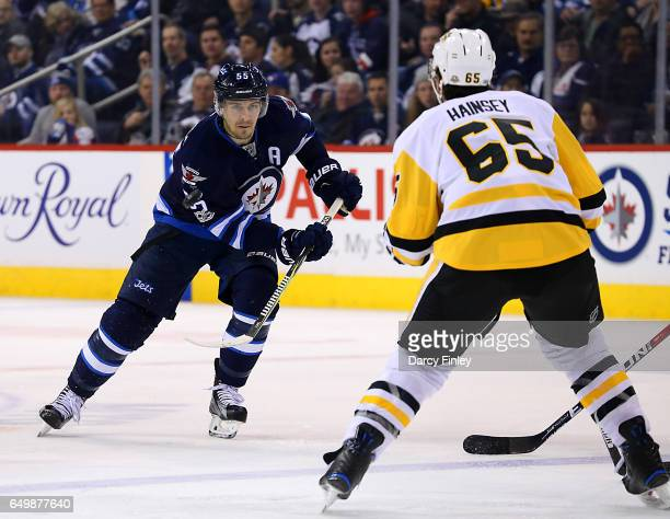 Mark Scheifele of the Winnipeg Jets follows the play down the ice as Ron Hainsey of the Pittsburgh Penguins defends during third period action at the...