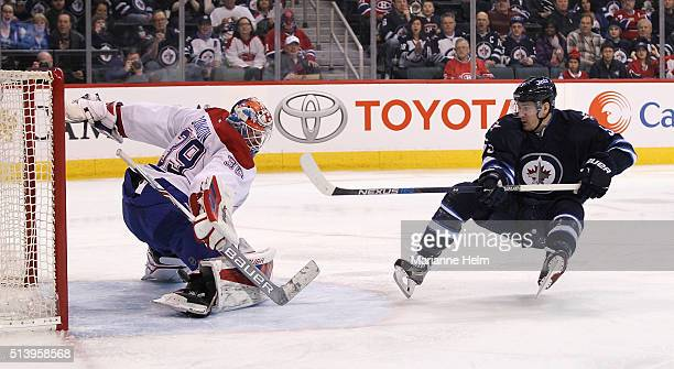 Mark Scheifele of the Winnipeg Jets gets the puck past Mike Condon of the Montreal Canadiens to score in second period action in an NHL game at the...