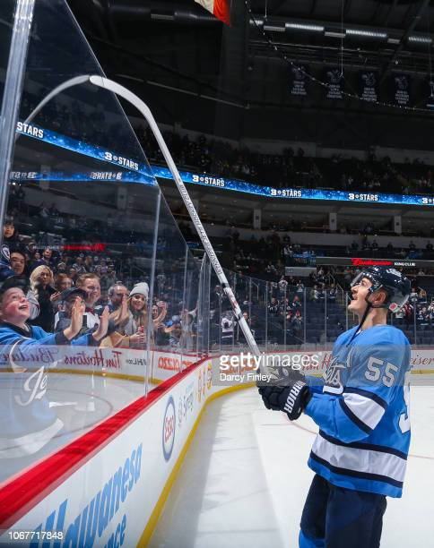 Mark Scheifele of the Winnipeg Jets gives a souvenir stick over the glass after receiving first star honours following a 52 victory over the New...