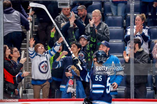 Mark Scheifele of the Winnipeg Jets gives a souvenir stick to a fan after receiving first star honours following a 43 victory over the New York...