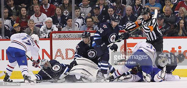 Mark Scheifele of the Winnipeg Jets helps out goaltender Ondrej Pavelec as Torrey Mitchell of the Montreal Canadiens tries to score in second period...