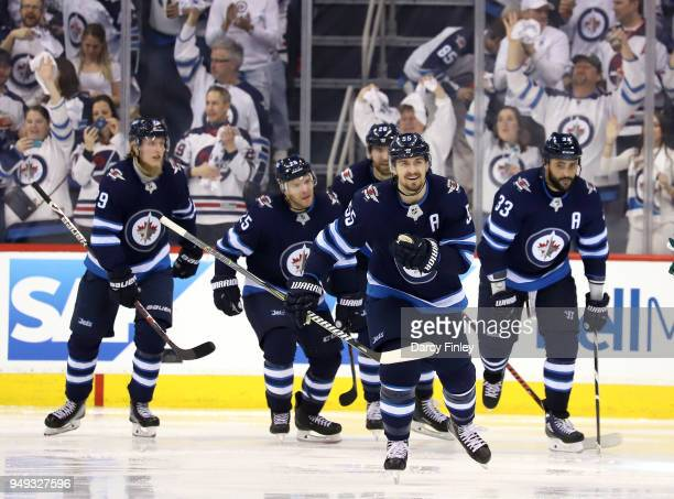 Mark Scheifele of the Winnipeg Jets is all smiles as he leads teammates Patrik Laine Paul Stastny Blake Wheeler and Dustin Byfuglien to the bench...