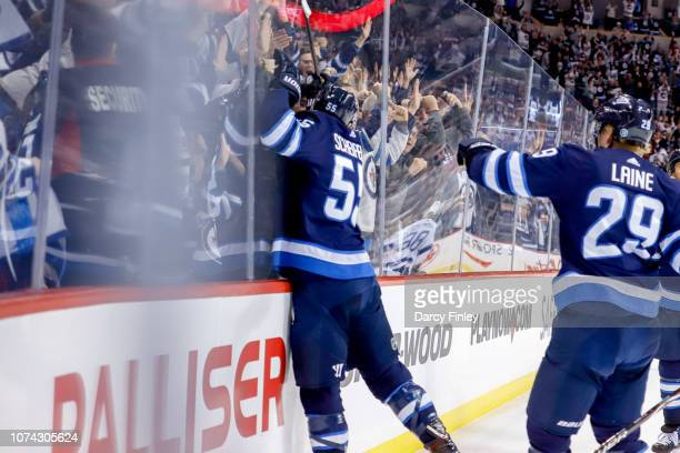 Mark Scheifele of the Winnipeg Jets jumps into the boards as he celebrates his overtime winning goal against the Tampa Bay Lightning at the Bell MTS...