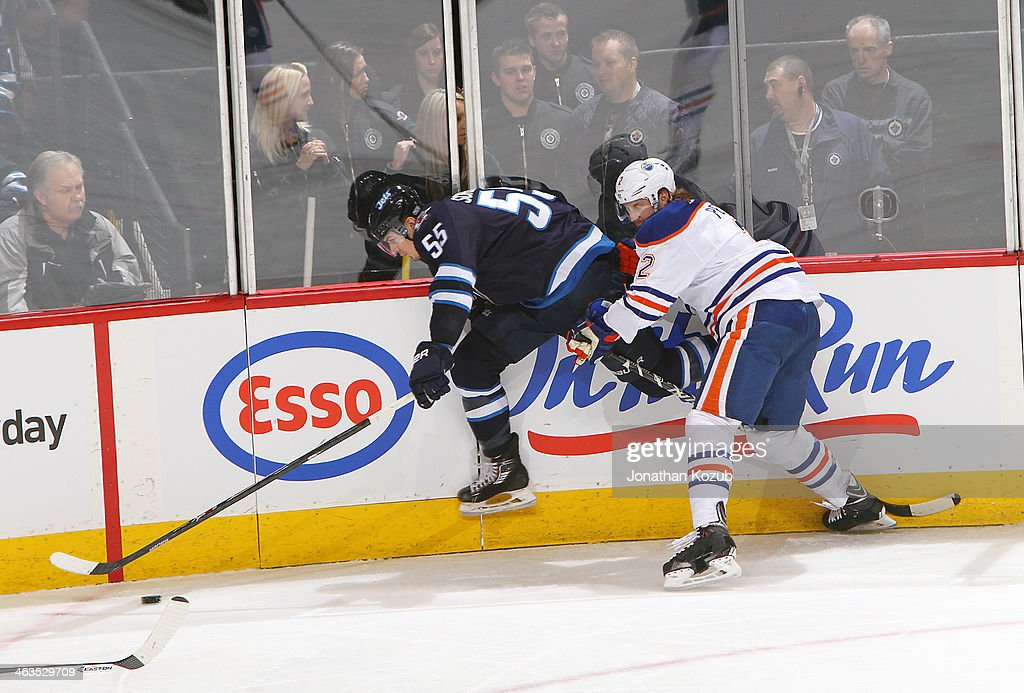 Mark Scheifele #55 of the Winnipeg Jets jumps past the check of Jeff Petry #2 of the Edmonton Oilers as he plays the puck along the boards during third period action at the MTS Centre on January 18, 2014 in Winnipeg, Manitoba, Canada.
