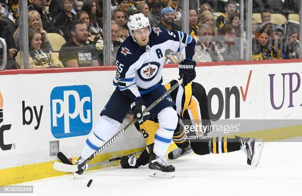 Mark Scheifele of the Winnipeg Jets makes a pass under pressure from Brian Dumoulin of the Pittsburgh Penguins during the game at PPG PAINTS Arena on...