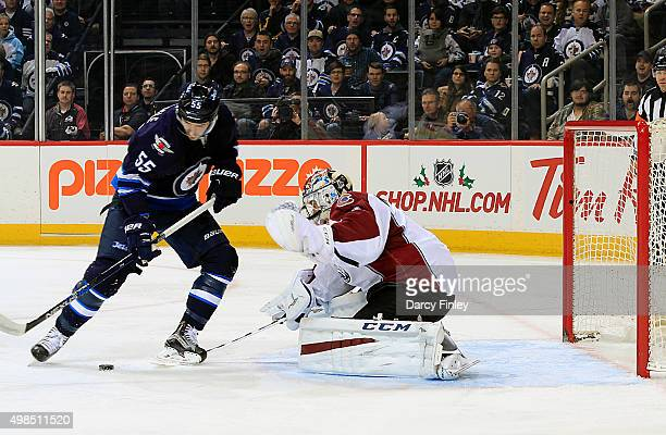 Mark Scheifele of the Winnipeg Jets pays the puck in front of goaltender Semyon Varlamov of the Colorado Avalanche during first period action at the...