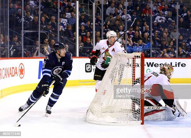 Mark Scheifele of the Winnipeg Jets plays the puck around the net as goaltender Mike Condon of the Ottawa Senators guards the net during second...