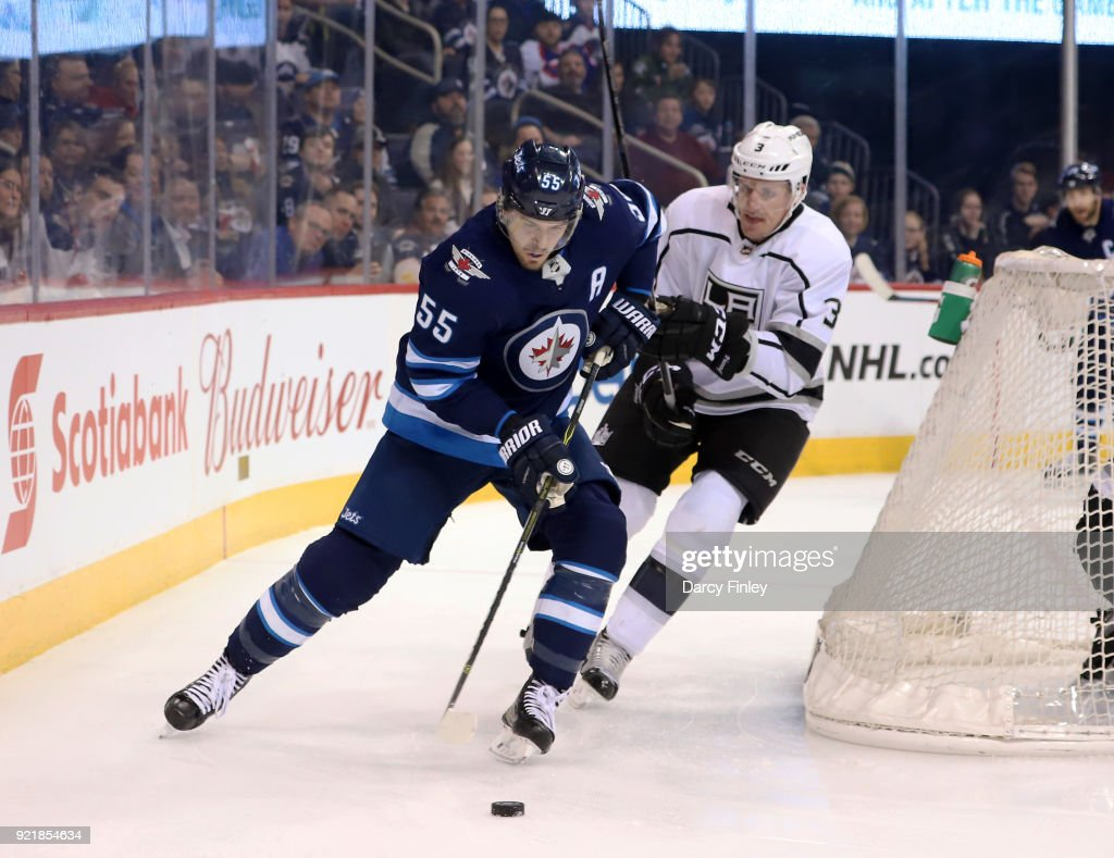 Mark Scheifele #55 of the Winnipeg Jets plays the puck away from Dion Phaneuf #3 of the Los Angeles Kings during third period action at the Bell MTS Place on February 20, 2018 in Winnipeg, Manitoba, Canada.