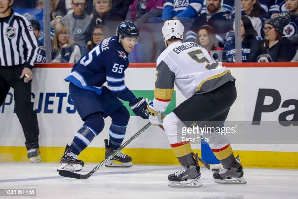 Mark Scheifele of the Winnipeg Jets plays the puck down the ice as Deryk Engelland of the Vegas Golden Knights defends during first period action at...