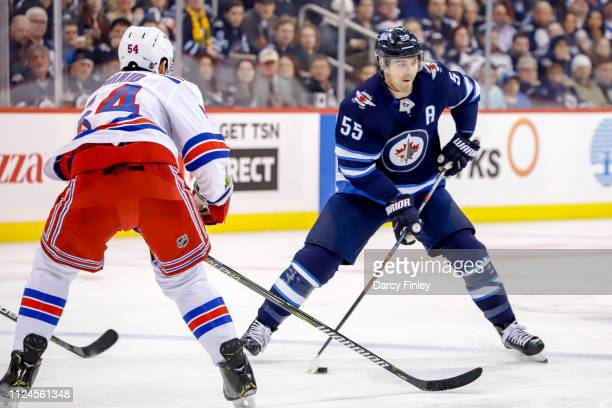 Mark Scheifele of the Winnipeg Jets plays the puck down the ice as Adam McQuaid of the New York Rangers defends during second period action at the...