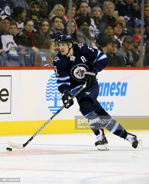 Mark Scheifele of the Winnipeg Jets plays the puck down the ice during first period action against the Carolina Hurricanes at the Bell MTS Place on...