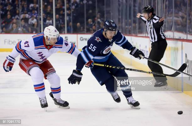 Mark Scheifele of the Winnipeg Jets plays the puck past a defending Steven Kampfer of the New York Rangers during first period action at the Bell MTS...