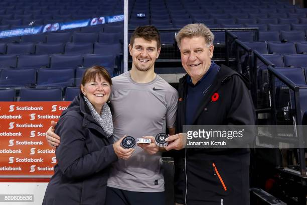 Mark Scheifele of the Winnipeg Jets poses with his parents Mary Lou and Brad after scoring his second career hat trick in a 52 victory over the...