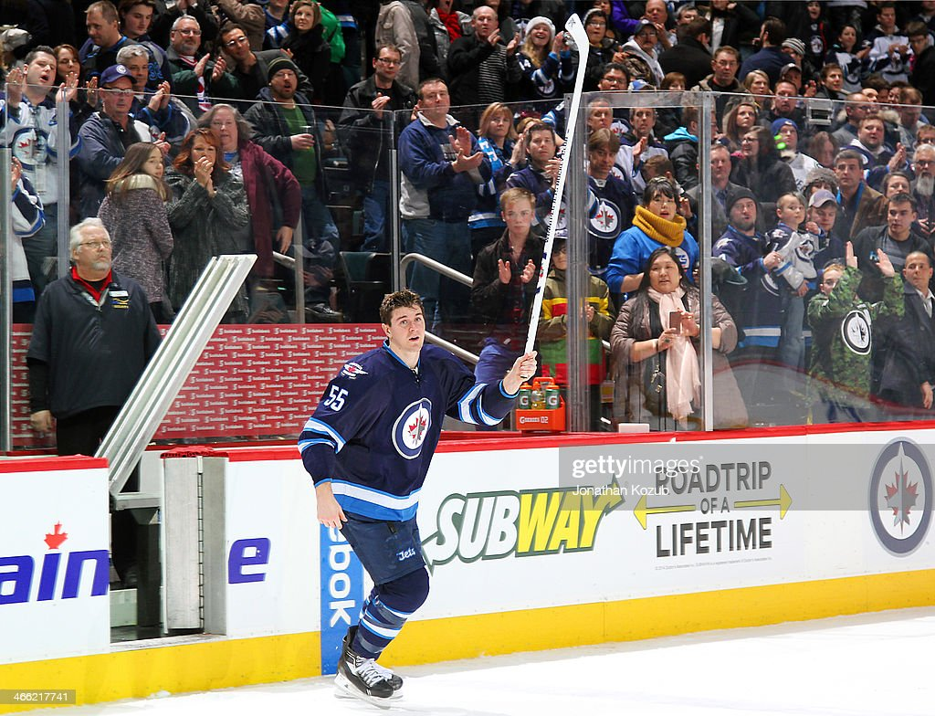 Mark Scheifele #55 of the Winnipeg Jets raises his stick in a salute to the fans after receiving third star honors following a 4-3 victory over the Vancouver Canucks at the MTS Centre on January 31, 2014 in Winnipeg, Manitoba, Canada.