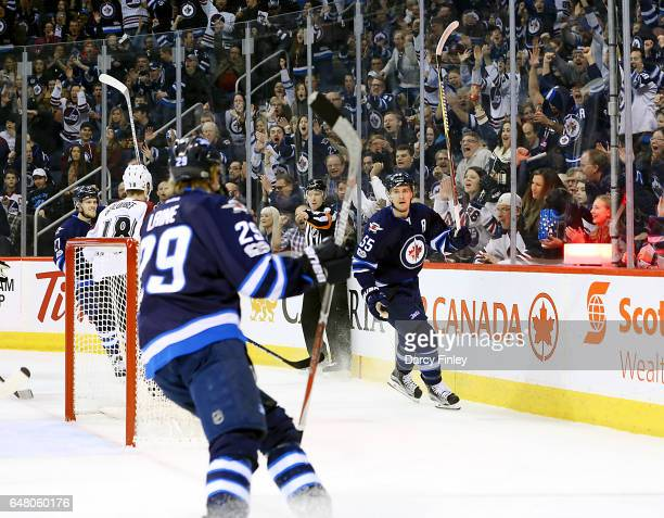 Mark Scheifele of the Winnipeg Jets raises his stick in celebration after scoring a first period goal against the Colorado Avalanche at the MTS...