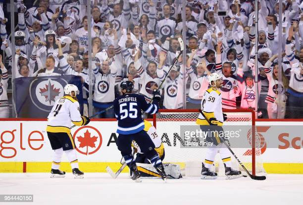 Mark Scheifele of the Winnipeg Jets raises his stick in celebration after teammate Patrik Laine scores a late third period goal against the Nashville...
