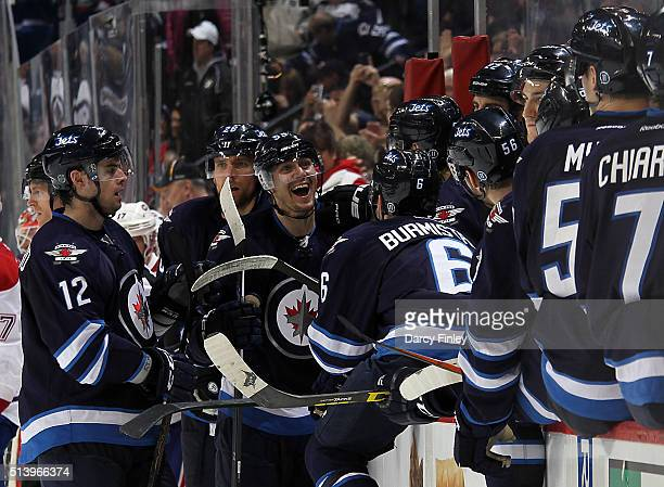 Mark Scheifele of the Winnipeg Jets shares a laugh with teammates at the bench after scoring his first career hat trick against the Montreal...