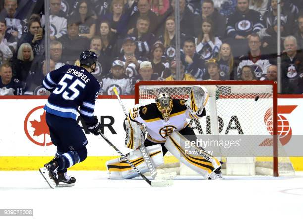 Mark Scheifele of the Winnipeg Jets shoots the puck into the net past goaltender Anton Khudobin of the Boston Bruins for a shootout goal at the Bell...